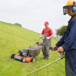 Gardeners mowing lawn with gas trimmer and lawnmower machine